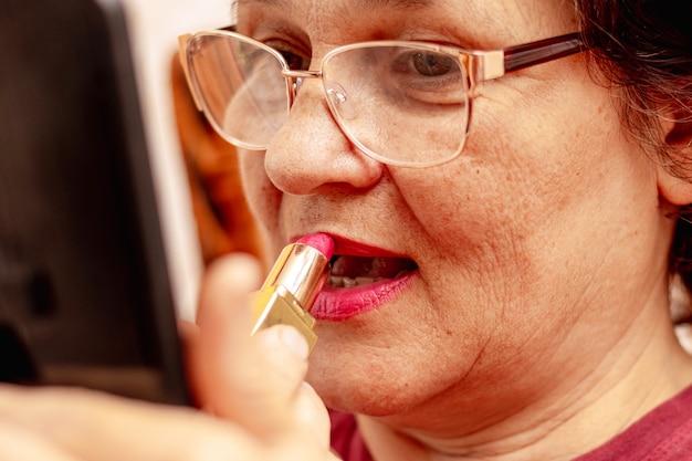 Uma senhora idosa pinta os lábios com batom, cuidando de sua beleza. mulher idosa séria passando batom na frente do espelho