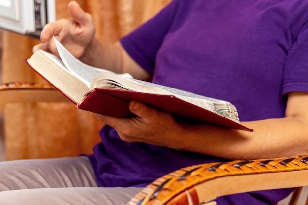 Uma senhora idosa se senta em uma cadeira e lê a bíblia
