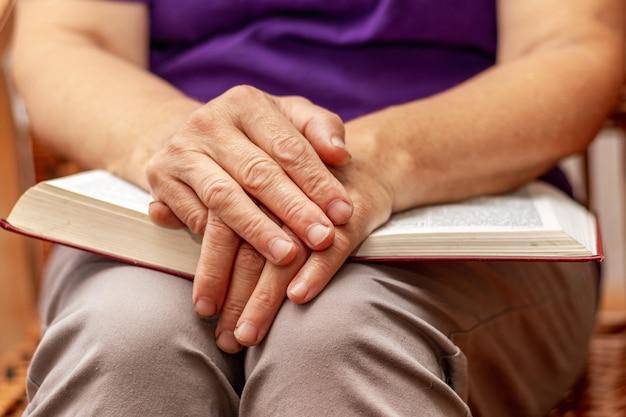 Uma senhora idosa se senta em uma cadeira, segura uma bíblia no colo e ora