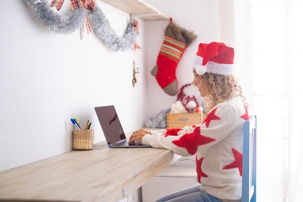 Uma senhora solteira em casa nas férias de natal usando o computador na estação de trabalho - apartamento branco e brilhante - festa de dezembro de ano novo - mulher inteligente e trabalhadora