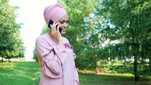 Uma senhora sorridente com um vestido longo roxo falando no smartphone
