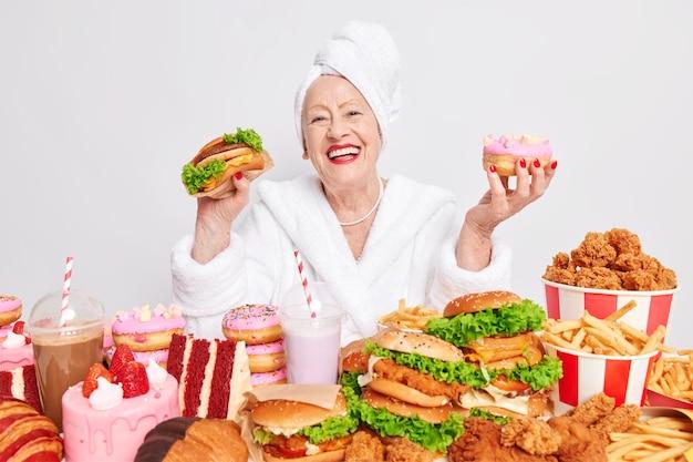 Uma senhora sorridente e alegre se sentindo muito feliz segurando um hambúrguer delicioso e um donut usando um roupão de banho e uma toalha na cabeça comendo junk food