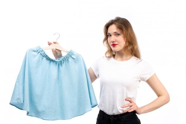 Uma senhora vista frontal na camisa branca e calça preta, segurando a saia azul no branco