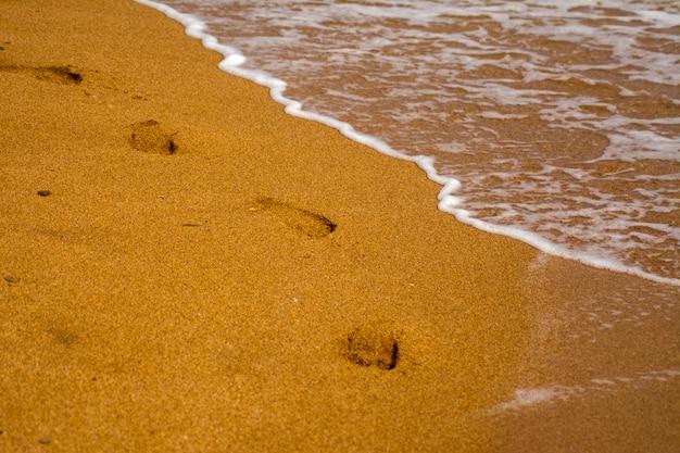 Uma sequência de pegadas nuas na areia. ondas na costa do mar, praia arenosa. espuma na água do mar.