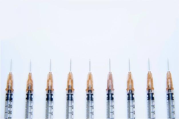 Uma série de seringas de insulina com agulhas em fundo branco