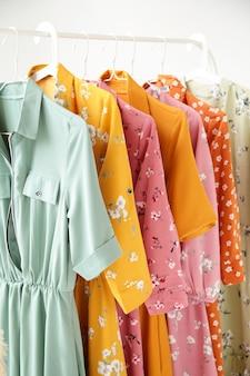 Uma série de vestidos de moda feminina em cabides em um armário branco para o verão e a primavera. vista do topo