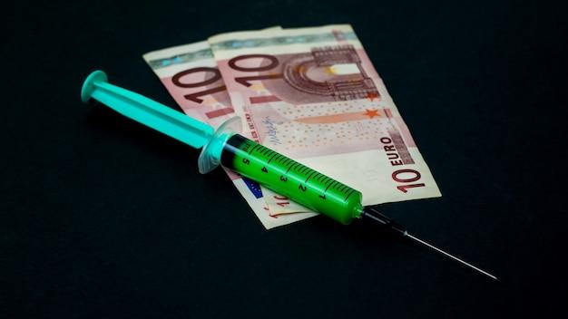 Uma seringa com uma vacina verde em um fundo preto. conceito de vacinação da população. remédio pago.