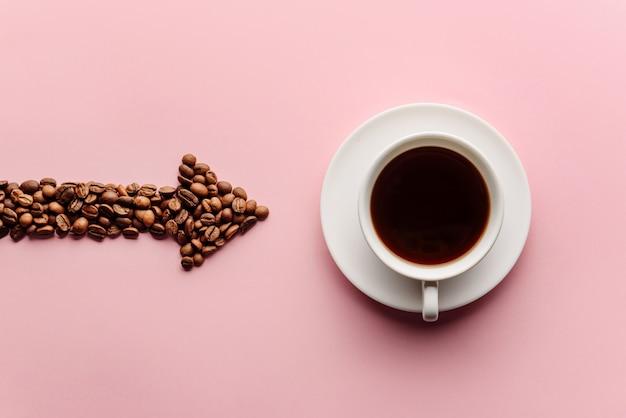 Uma seta alinhada com grãos de café indica uma xícara de café próxima. conceito de amor café.