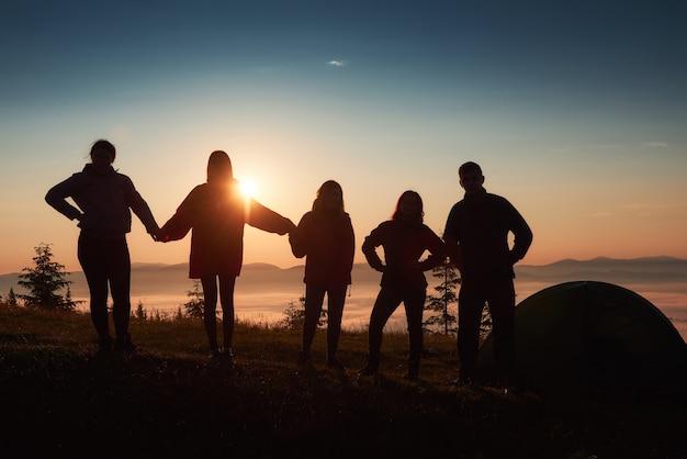 Uma silhueta de um grupo de pessoas se diverte no topo da montanha perto da tenda durante o pôr do sol.