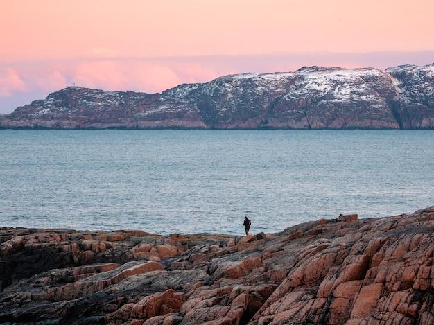 Uma silhueta, uma figura em um penhasco íngreme do céu do ártico do pôr do sol.