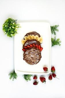 Uma sobremesa choco vista de cima com bananas fatiadas e um prato branco com cobertura de morango, juntamente com plantas de decoração e morangos inteiros na mesa branca, chá doce de frutas