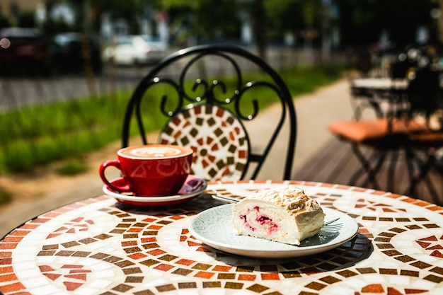 Uma sobremesa de merengue e uma xícara de café cappuccino vermelha feita na hora em uma mesa de pedra de mosaico de um café