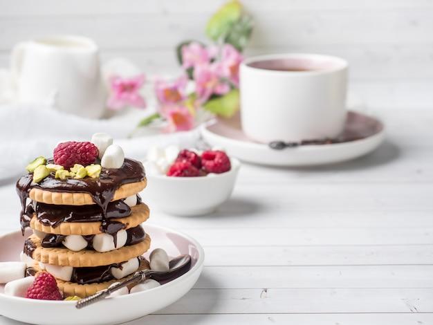 Uma sobremesa doce de um biscoito de chocolate framboesa e marshmallow xícara de café em uma mesa de luz