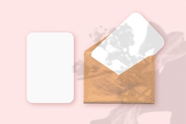 Uma sobreposição de sombras de plantas em um envelope com duas folhas de papel branco texturizado em um fundo de mesa rosa