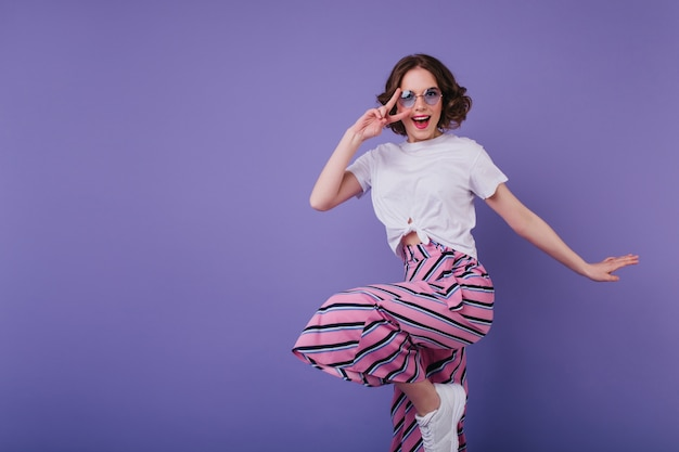 Uma sonhadora garota branca de tênis elegantes, pulando na parede roxa. mulher elegante de cabelos curtos e óculos escuros brincando durante a sessão de fotos.