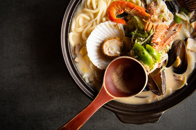 Uma sopa de vegetais frescos é colocada em uma mesa acinzentada Foto Premium