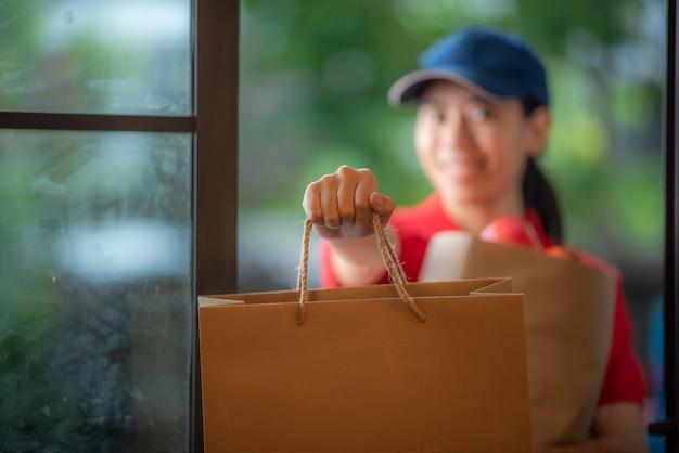 Uma sorridente jovem mulher asiática entrega mercadorias na frente da porta da casa, conceito de varejo online, entrega rápida, conceito de estilo de vida urbano, serviço de compras online, transporte.