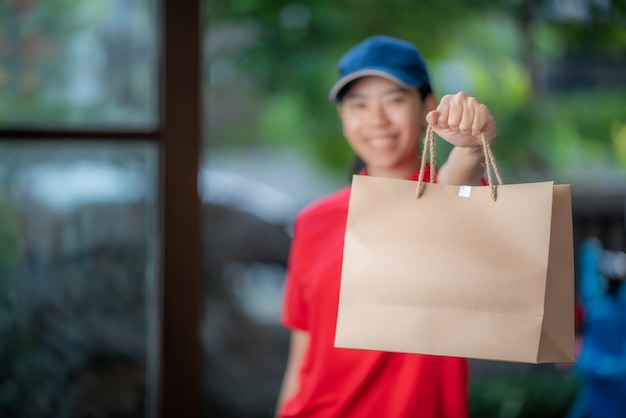 Uma sorridente jovem mulher asiática entrega mercadorias na frente da porta da casa, conceito de varejo online, entrega rápida, conceito de estilo de vida urbano, serviço de compras online, transporte. Foto Premium