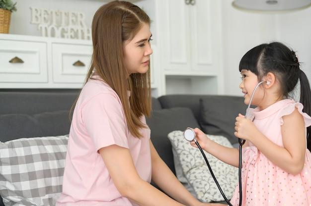 Uma sorridente menina asiática brincando de médico e ouvindo a mãe com estetoscópio em casa