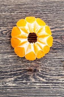 Uma suculenta tangerina madura de cor amarela cortada em fatias com uma faca, descascada