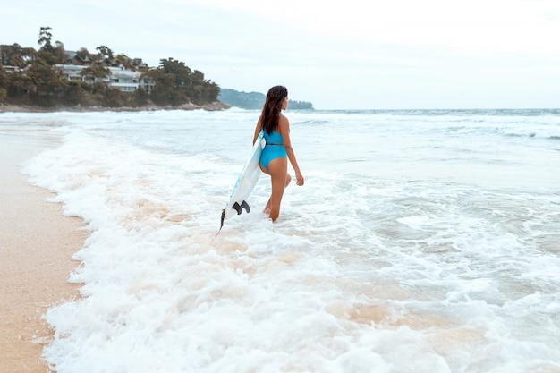 Uma surfista linda com um corpo esbelto em biquíni e com prancha se divertindo na praia.