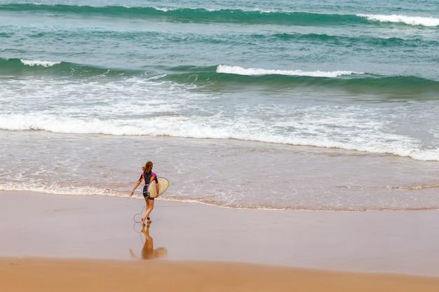 Uma surfista na praia entrando no oceano com sua prancha