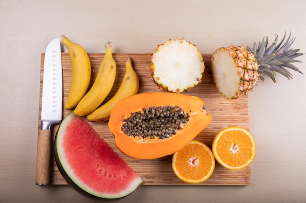 Uma tábua de cortar com frutas cortadas em cima e uma faca mamão melancia abacaxi laranjas e bananas