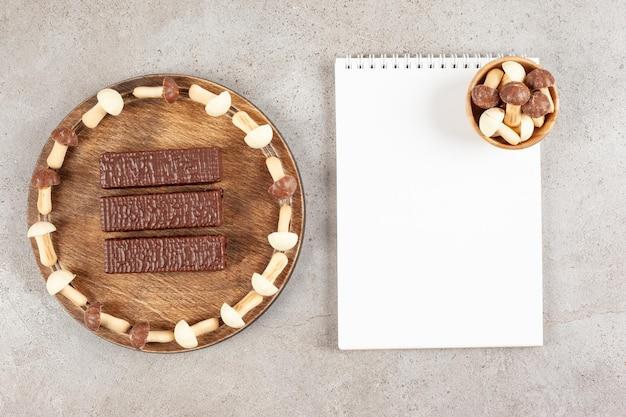 Uma tábua de cortar de madeira com três chocolates e folha de papel.