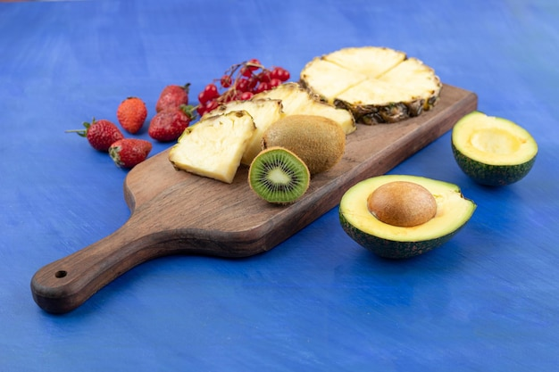 Uma tábua de cortar de madeira fatiada abacaxi com kiwi na superfície azul