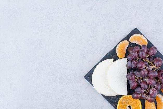 Uma tábua de cortar escura com fatias de queijo e frutas. foto de alta qualidade