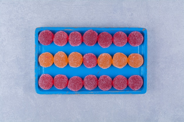 Uma tábua de madeira azul cheia de geleias açucaradas de vermelho e laranja