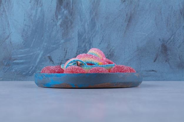 Uma tábua de madeira azul com balas de geleia vermelhas açucaradas com alcaçuz doce de arco-íris