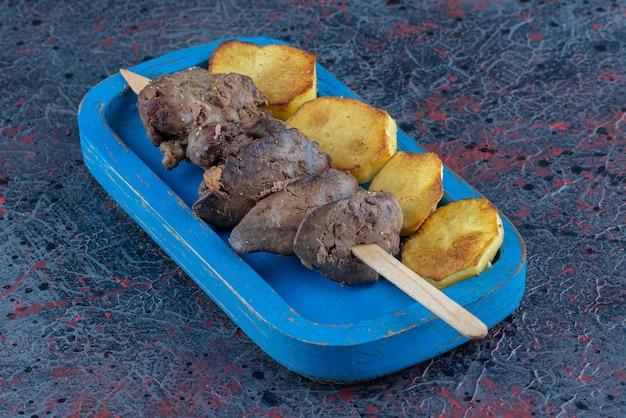 Uma tábua de madeira azul com batata frita com carne
