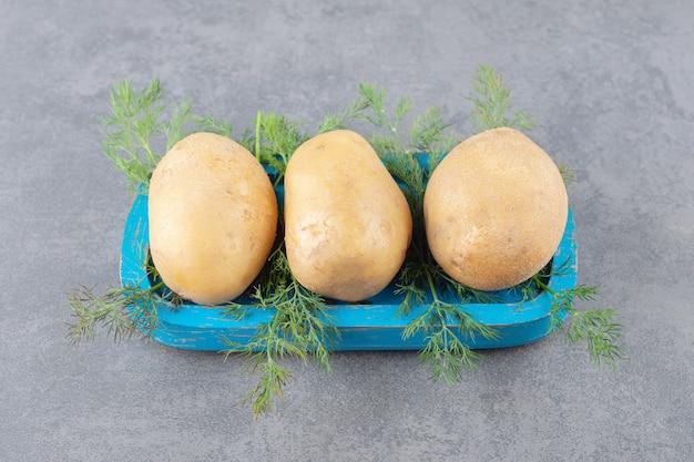 Uma tábua de madeira azul com batatas cruas com endro fresco