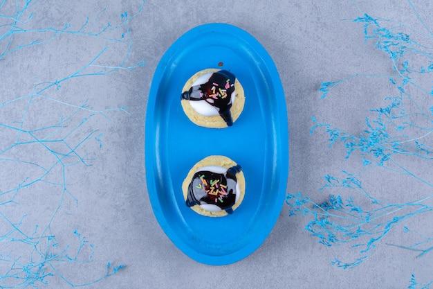 Uma tábua de madeira azul com biscoitos doces com granulado colorido e calda de chocolate