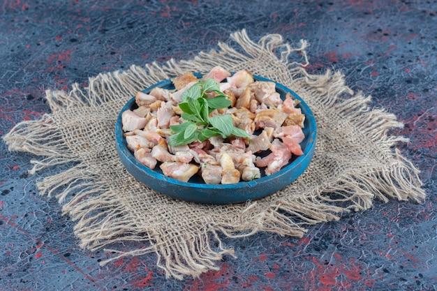 Uma tábua de madeira azul com fatias de carne de frango e hortelã