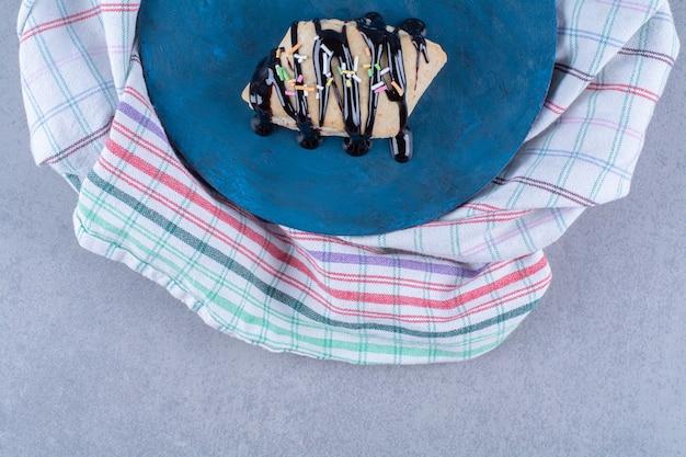 Uma tábua de madeira azul de massa doce com granulado colorido e calda de chocolate.