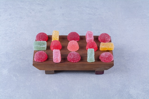 Uma tábua de madeira cheia de balas de gelatina açucaradas
