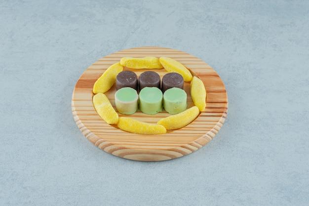 Uma tábua de madeira cheia de balas de mascar em forma de banana e balas de geleia