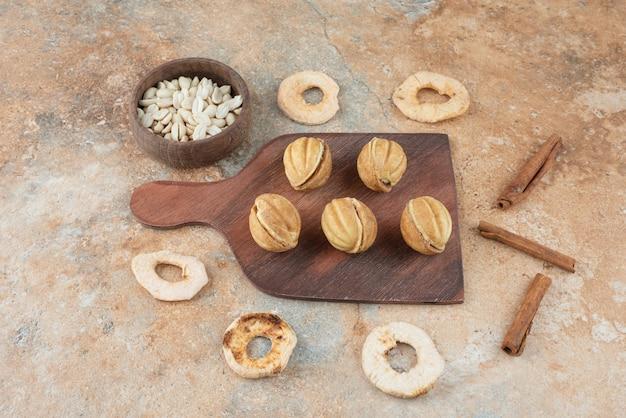 Uma tábua de madeira cheia de biscoitos doces e paus de canela