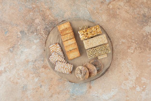 Uma tábua de madeira cheia de biscoitos doces e pedaços de amendoim