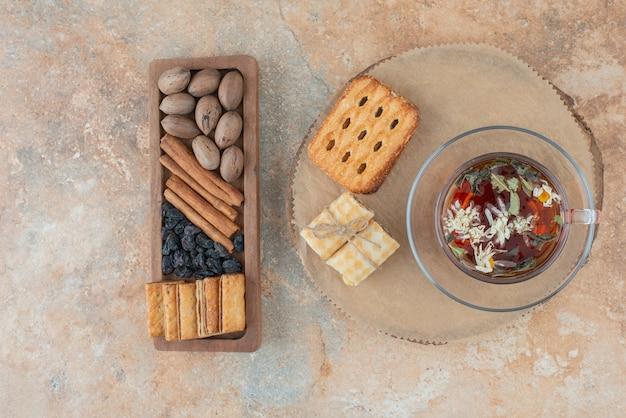 Uma tábua de madeira cheia de biscoitos doces e uma xícara de chá de ervas