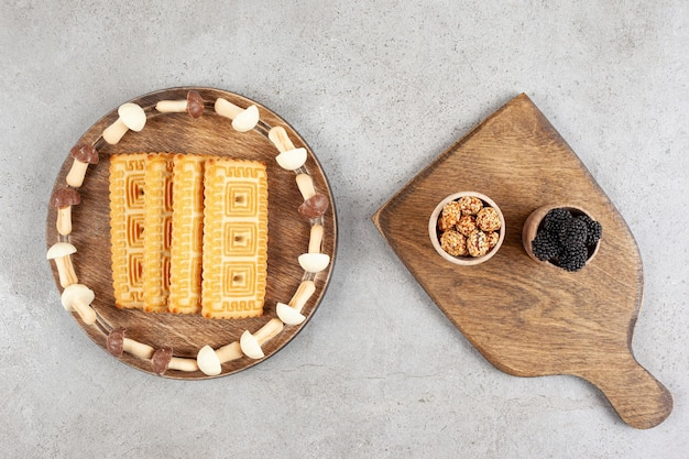 Uma tábua de madeira cheia de biscoitos e cogumelos doces.