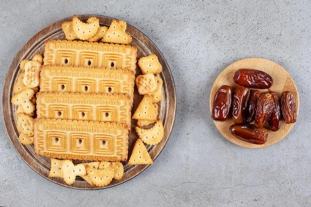 Uma tábua de madeira cheia de biscoitos na superfície de mármore