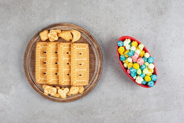 Uma tábua de madeira cheia de biscoitos na superfície de mármore.