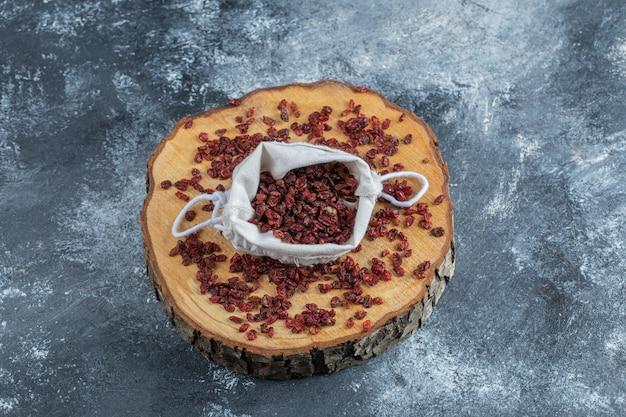 Uma tábua de madeira cheia de cranberries secas.