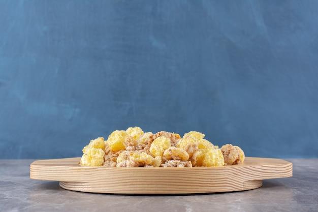 Uma tábua de madeira cheia de deliciosos cereais saudáveis para o café da manhã.