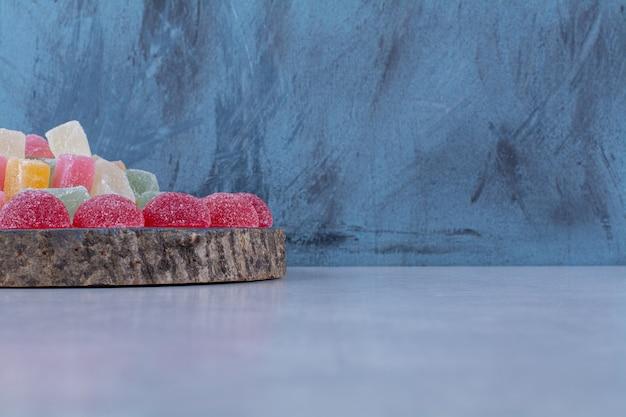 Uma tábua de madeira cheia de doces de gelatina açucarados coloridos.