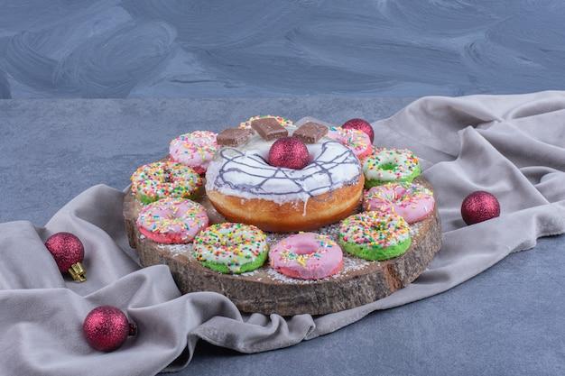 Uma tábua de madeira cheia de donuts doces e bolas de natal