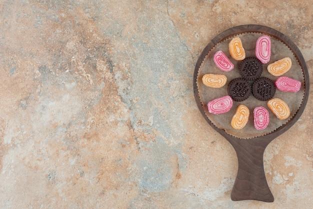 Uma tábua de madeira cheia de geleias e biscoitos